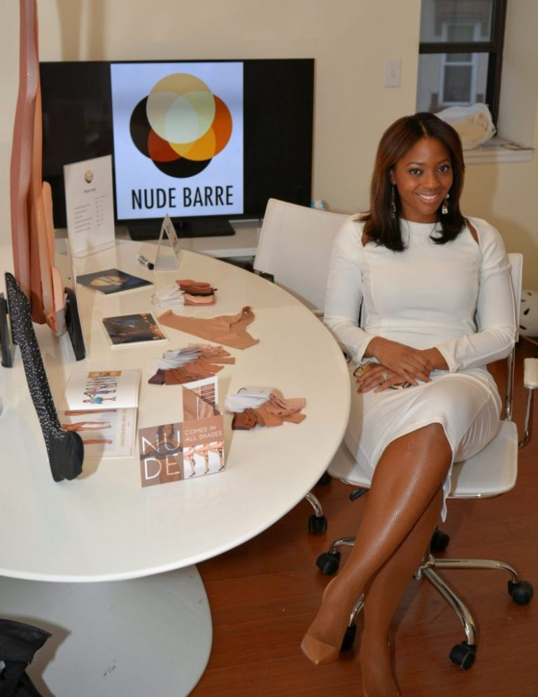 Erin Carpenter, CEO of Nude Barre, in white dress, sitting next to table where her products are displayed.