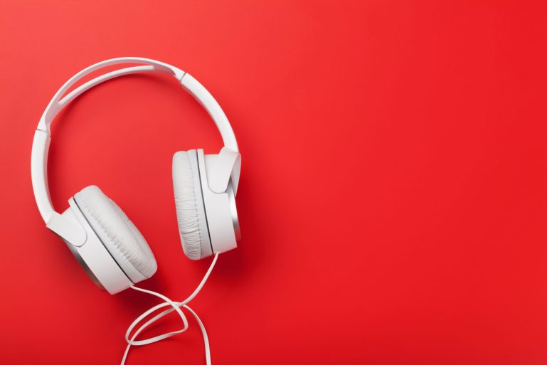 Music headphones on red background. Sound concept. Top view with copy space. Flat lay