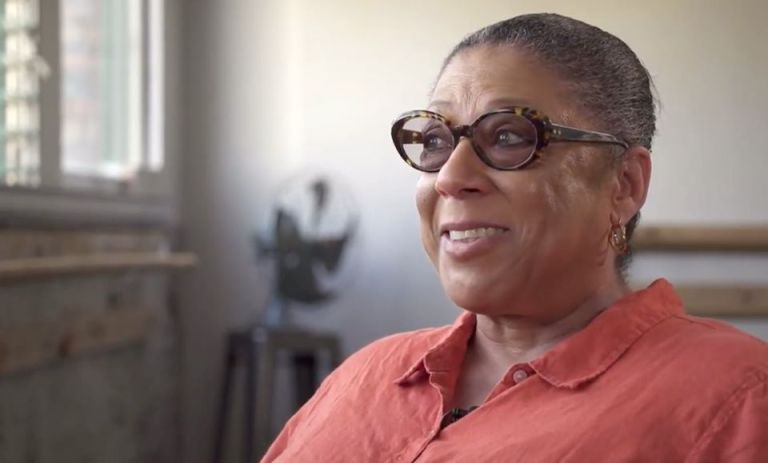 Klair Ethridge, a Black woman wearing glasses and a peach button-down shirt, smiles, looking off camera