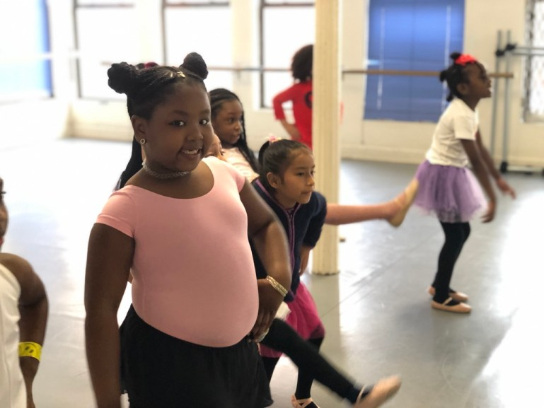 A young girl poses and smiles at the camera as her classmates dance around her