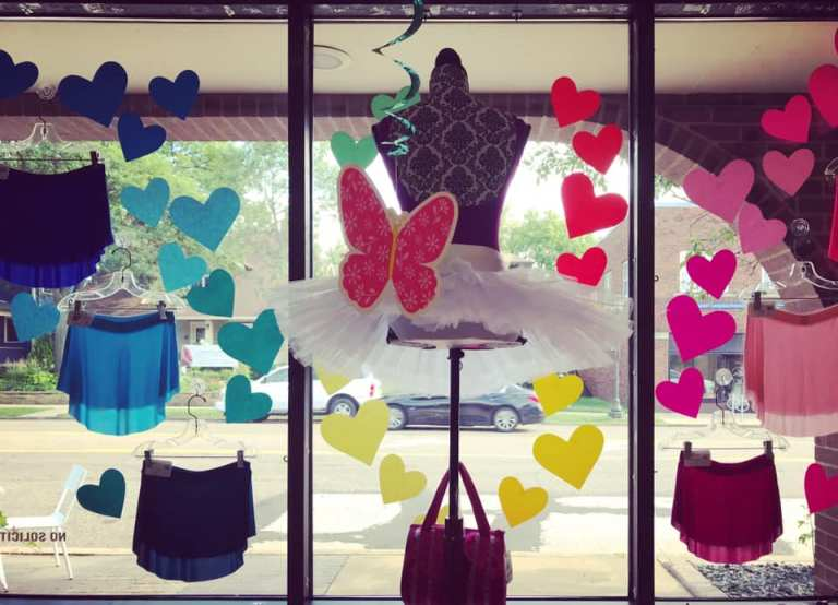 A window display featuring leotards, ballet skirts, and colorful paper hearts and butterflies
