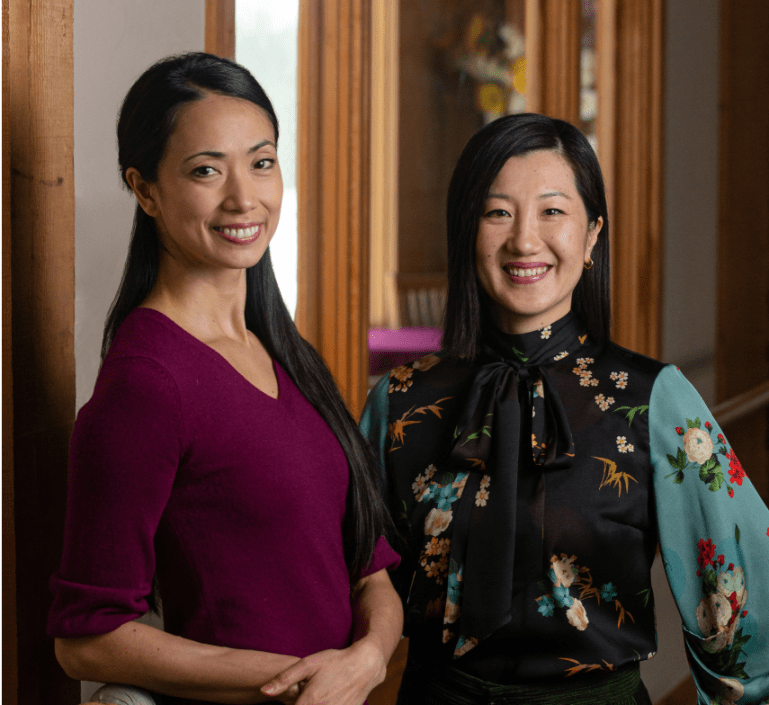 Stella Abrera and Sonja Kostich stand together in colorful blouses, smiling
