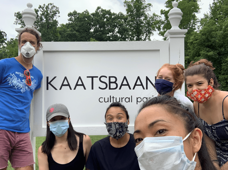 "Six masked Kaatsbaan staff members, including Abrera and Kostich, stand around a sign that says ""Kaatsbaan cultural park"""