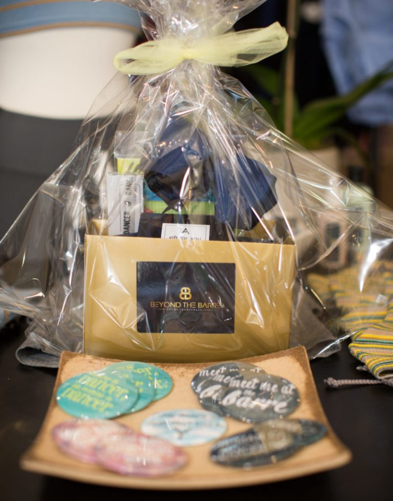 Display with cellophane-wrapped gift package with Beyond the Barre logo and dance buttons on the table in front.