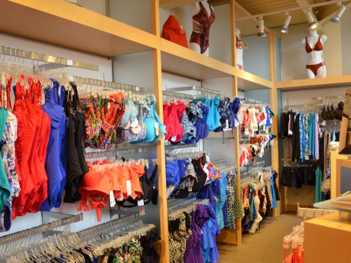 Light wood shelves with racks of colorful swimwear.
