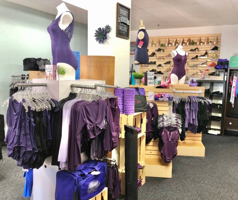 Purple dancewear displays with dance shoes in background.