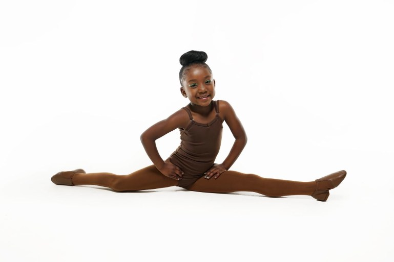 Young Black dancer doing splits, with matching brown flesh tone tights and shoes