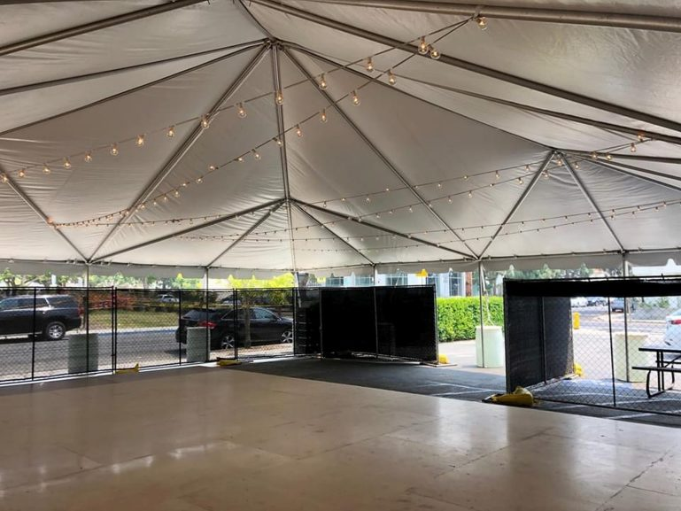 A large tent in a parking lot with a dance floor underneath. Strings of lights are strung across the top, and it is surrounded by a fence.
