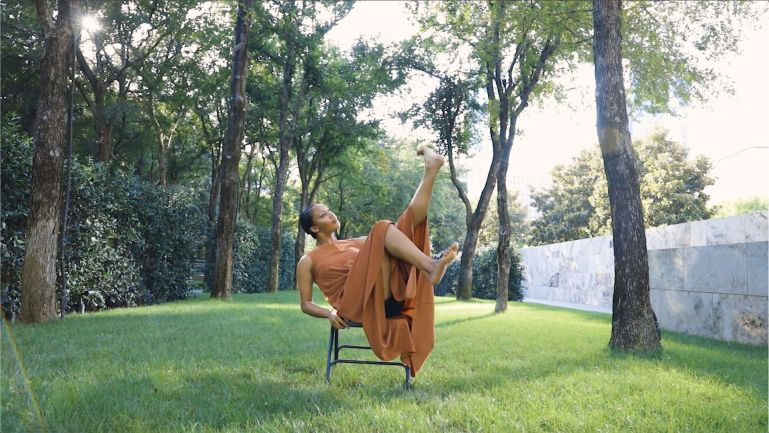 A video still of a dancers in a grassy, tree-lined backyard, leaning back in a chair with her legs in the air. She wears a long orange dress, and has her dark hair in a low bun