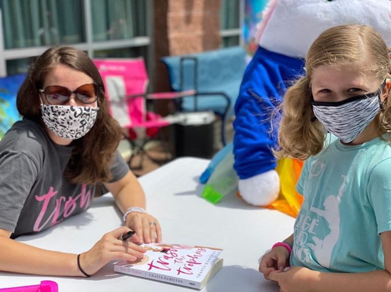"""Hamilton, masked, sits an outdoor table, holding her book called """"Trash the Trophies"""" and a sharpie. A young masked student stands on the other side of the table"""