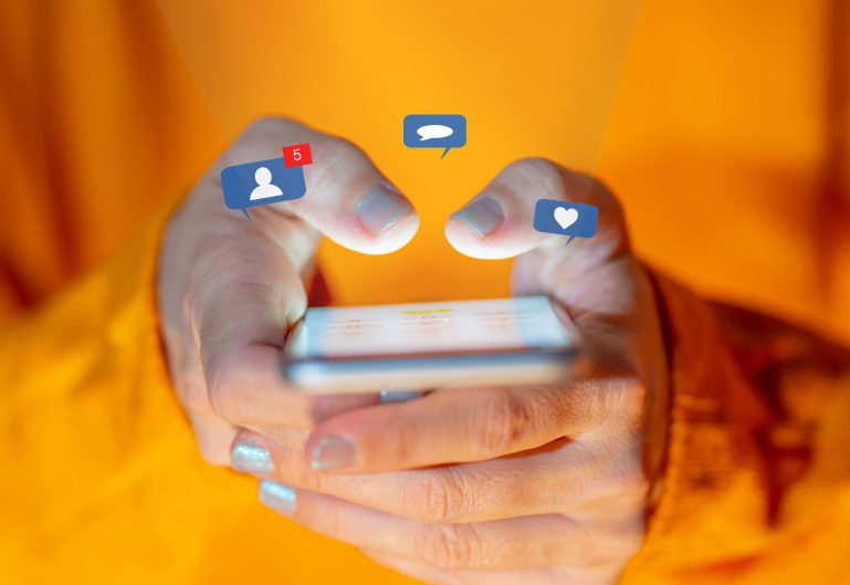 A close up of a woman's hands holding a phone, with animated notification alerts from various social media sites floating above the phone