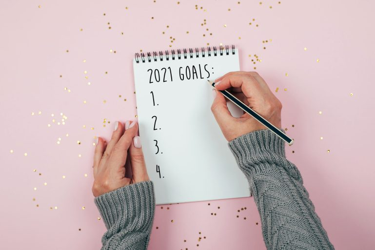 Woman's hand writing 2021 Goals in notebook decorated with Christmas decorations on the tricolor background. Top view, flat lay