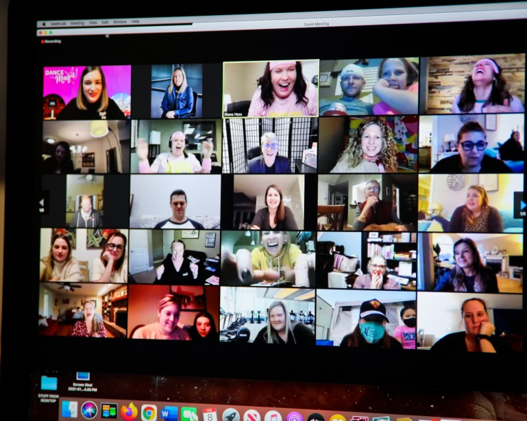A computer screen shows a Zoom room full of smiling, laughing faces, mostly women.