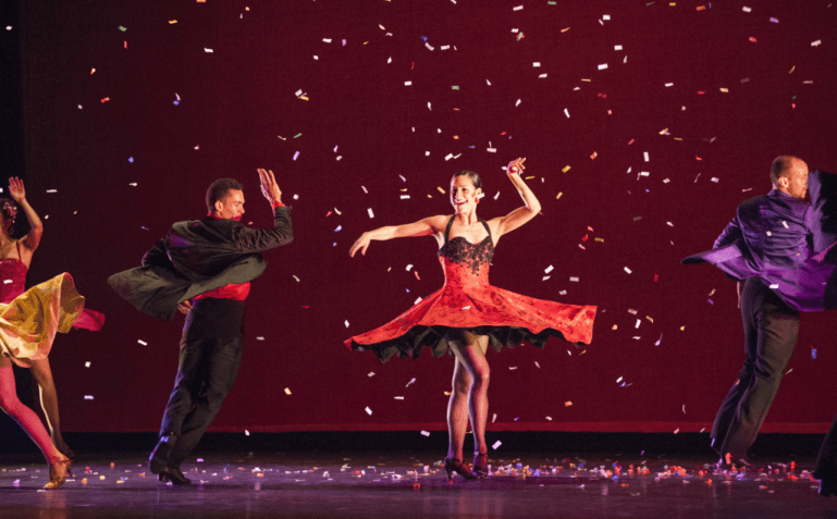 A woman in a black and red dress twirls onstage, sending her skirt flying around her. A man circles around her, and other couples surround them just off-camera. Confetti litters the stage and rains down around them.