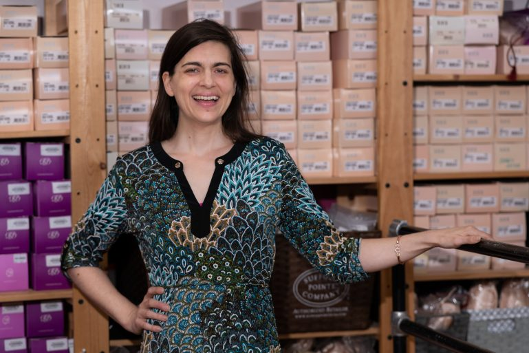 Jennifer Babb, a white woman with dark hair, stands in front of a wall of pointe shoes in boxes, holding onto a barre and smiling.