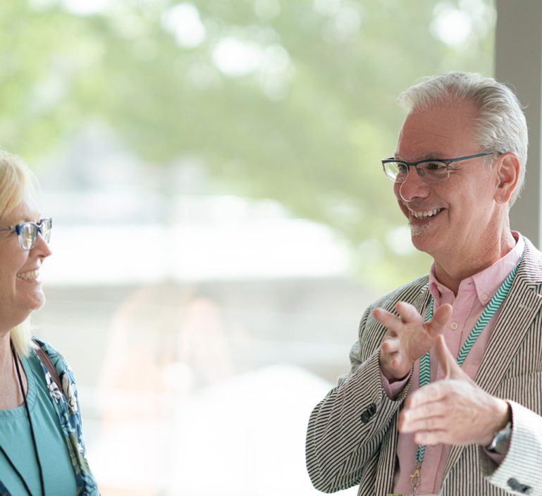 Gilbert Russell, man with gray hair, glasses, talking to woman on left with aqua dress