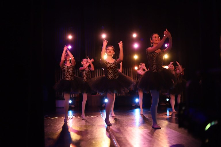 A group of teenage students perform a ballet dance at their recital, wearing black and gold costumes.