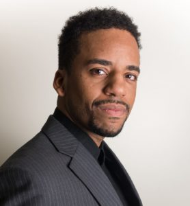 Roger Lee, a Black man with short dark hair and a goatee, looks at the camera from the side, softly smiling. He wears a black button down shirt and a grey striped jacket.