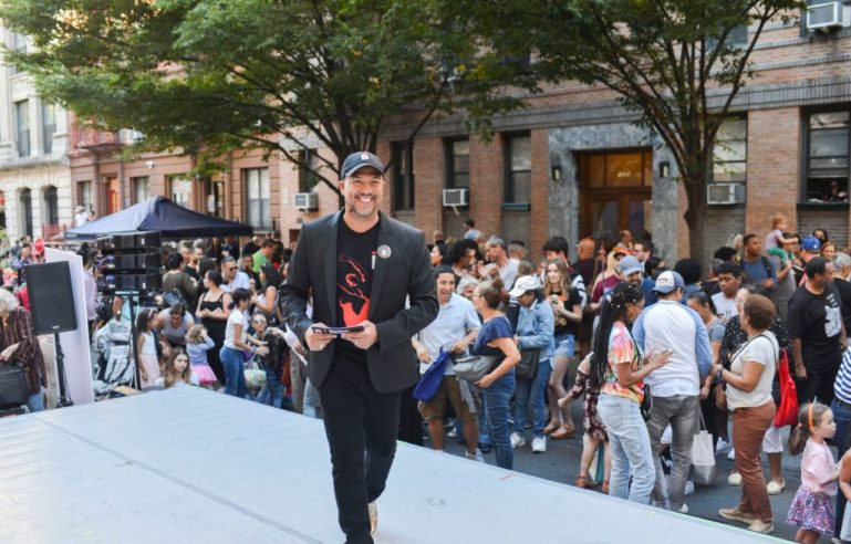 Eduardo Vilaro, a light-skinned Latino man, smiles and walks across an outdoor stage in the middle of a crowded street. He wears a baseball cap, a black t shirt and a black jacket.
