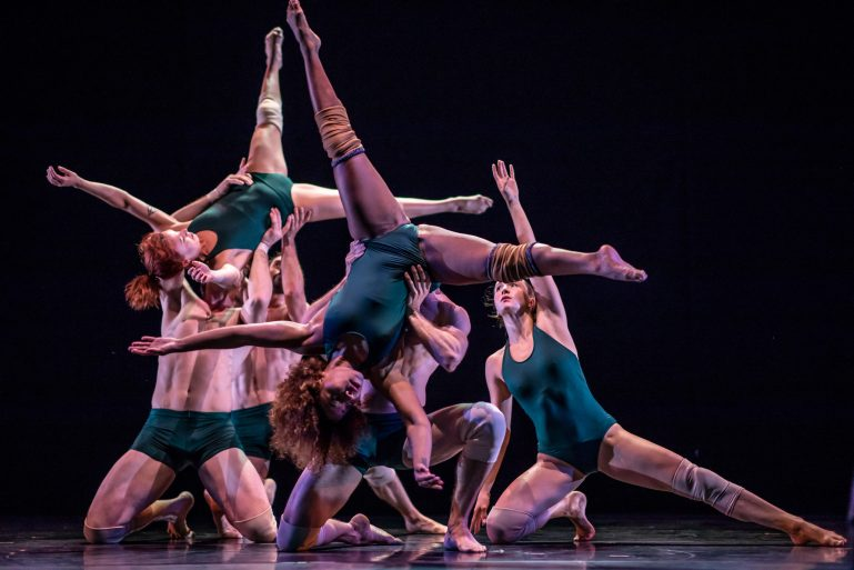 Pilobolus performs in dark blue leotards for the women and shorts for the men. Several men kneel on the ground, lifting women above their heads with legs extended into splits.
