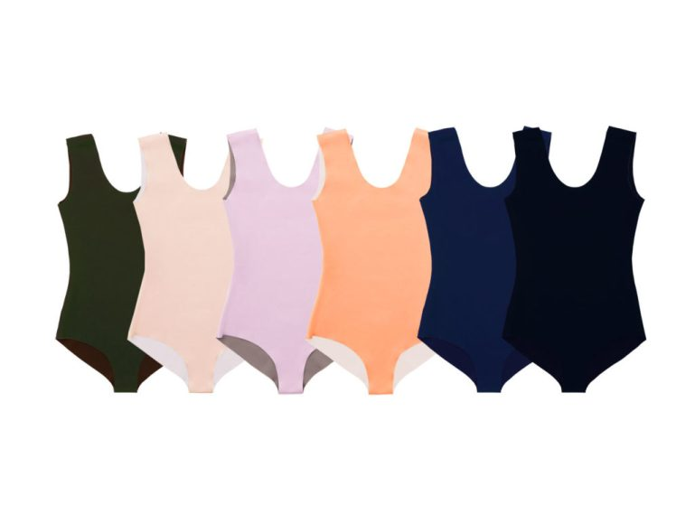 Five leotards—dark green, light pink, pink/purple, peach, navy and black—lined up next to each other, overlapping. They have a simple U-neck design and thick shoulder straps.