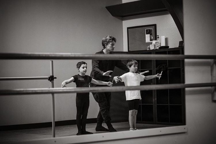 Harrison Ball stands behind two young boys, correcting one's second position arm placement.