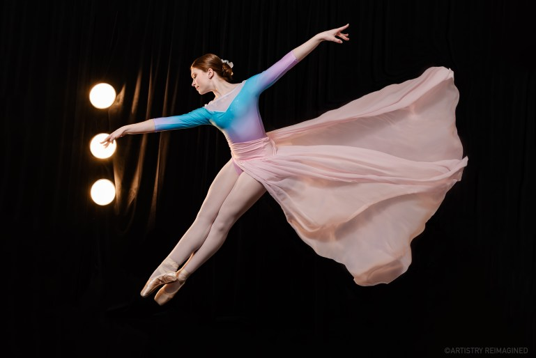 A teen dancer in a pastel long sleeved leotard, a long pink skirt and pointe shoes leaps into the air, feet pointed in fifth position and leaning slightly forward. Her skirt billows behind her
