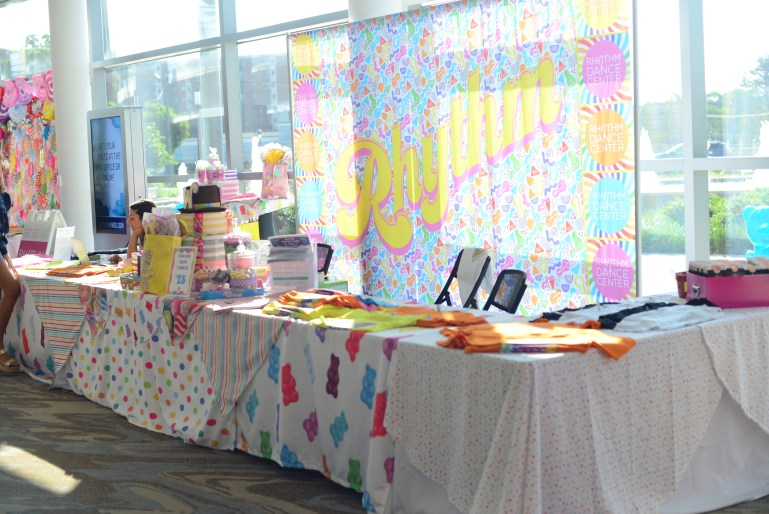 """A table full of goodies is in front of a large, colorful banner that says """"Rhythm."""" There are brightly colored shirts and other items for sale, and a woman sits behind the table."""