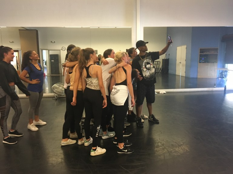 A group of teen dancers gather around for a selfie with a master teacher, a Black man in a black hat who holds the phone out for the photo.