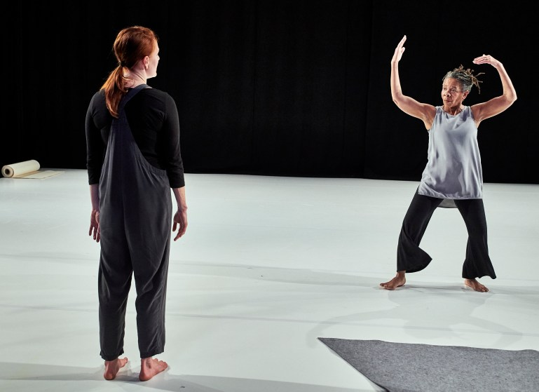 Two women stand on a white-floored stage. Angie Hauser, in the foreground, faces upstage and looks at Bebe Miller. She is wearing black overalls and has her red hair in a ponytail. Miller, mid-motion with her arms above her head, looks back at Hauser. Her light gray shirt and the cuffs of her pants swing with her movement.