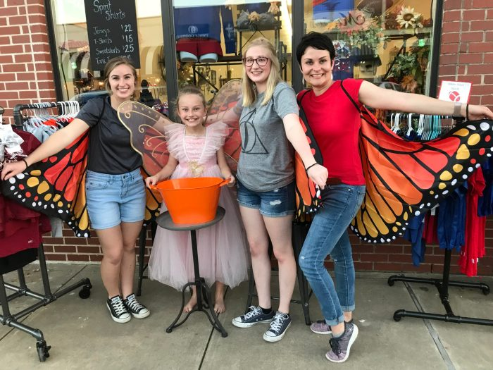 Dance store sidewalk sale, showing storeowner and staff wearing monarch butterfly dress-up wings and young girl in tulle ballet outfit with pink wings in middle.