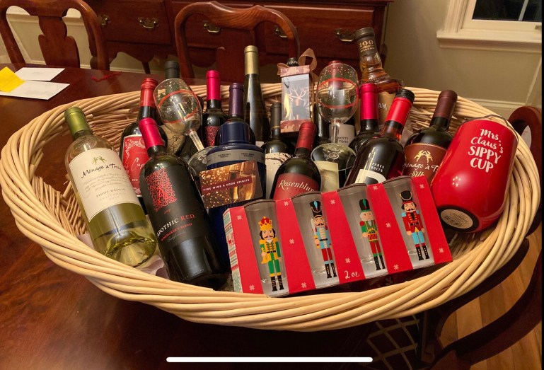 A large wicker gift basket sits on a table. It contains around 10 bottles of wine, a bottle of liquor, and some festive wine glasses.