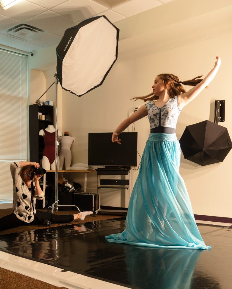 Jennifer Fitzpatrick sits on the floor in the splits, holding a large camera up to her face. A young dancer in a long blue skirt, the subject of the photoshoot, twirls for the camera