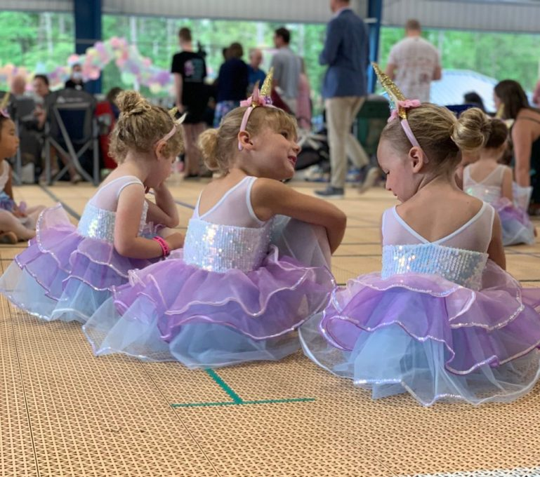 Three young dancers in purple and blue tutus and unicorn horns sit and chat backstage at the outdoor recital.