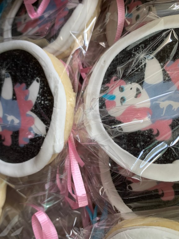 Cookies decorated with a dancing unicorn wrapped in clear plastic bags and tied with pink ribbons