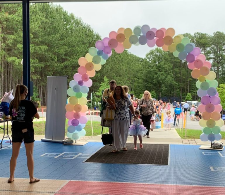 A group of parents and children walk under a balloon arch into the recital venue.