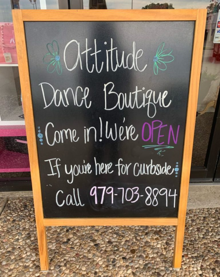 Chalkboard sign advertising phone number for curbside pickup at Attitude Dance Boutique.