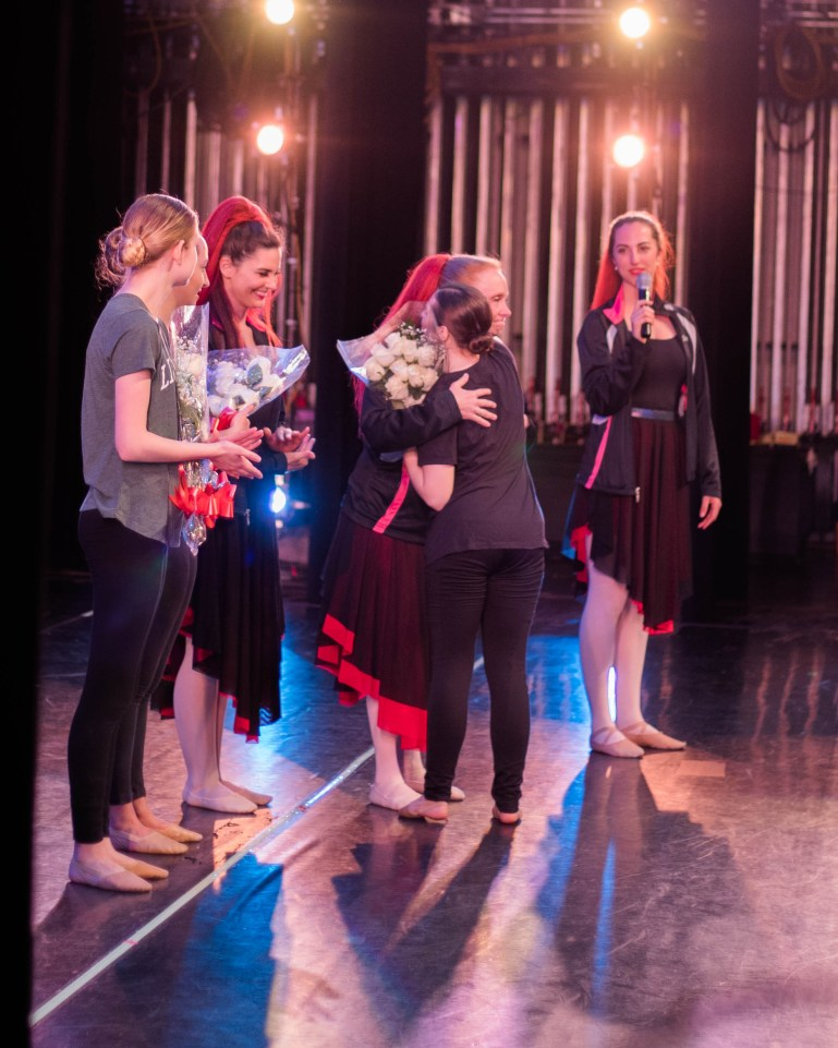 Four dance teachers, in costume from performing, hand out flowers to senior dancers at the end of a recital. They are onstage, with stage lights shining on them, and one student hugs a teacher.