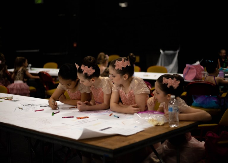 A group of elementary-aged students backstage at a recital color on a large piece of paper. They are in pink costumes and have bows in their hair.