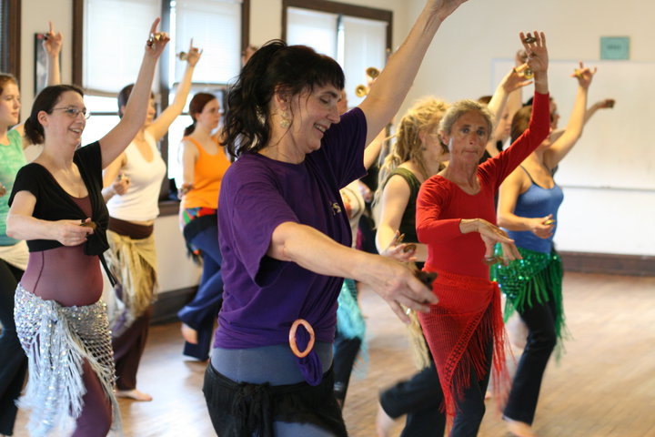 Women in bright colors and skirts with fringe dance in a bright studio, holding one arm up, slightly rounded, and one arm in front of them.