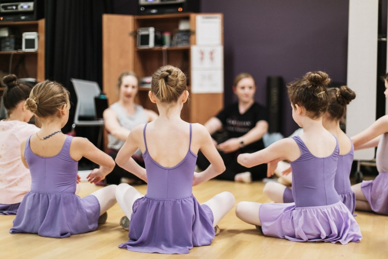 A group of young dancers in purple leotards and skirts, as well as a few teachers, sit in a circle and practice first position with their arms.