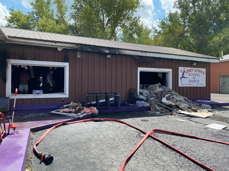A studio, seen from the parking lot, with burn stains and debris spilling out a large window. A fire hose lays across the parking lot.
