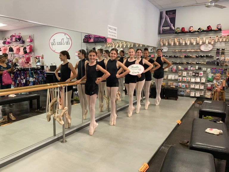 Row of young dancers in black leotards standing at the barre on pointe in The Dance Bag store, where they've been fitted for pointe shoes.