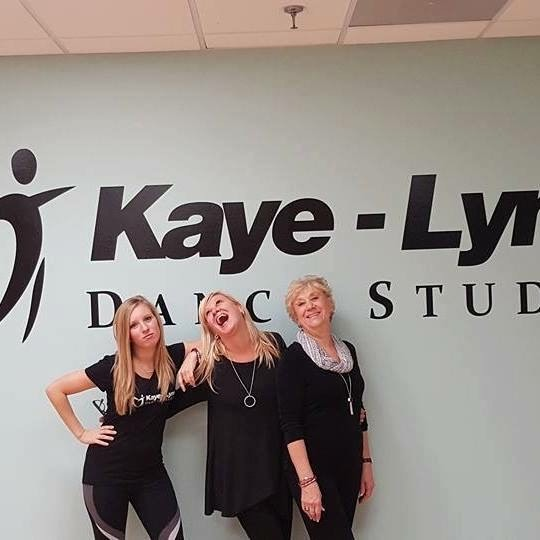 The three women of Kaye-Lynn Dance Studio stand together in front of a wall with the studio's logo. They all wear black and laugh, with arms around each other