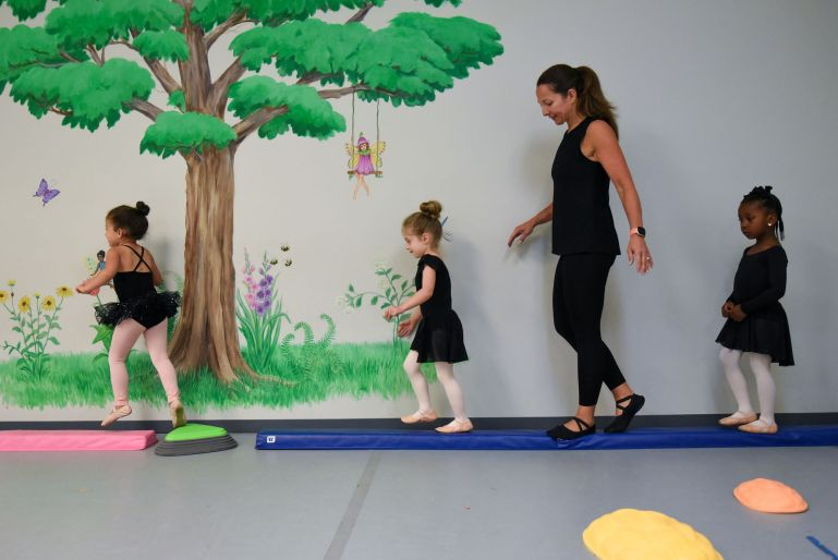 Kim Black walks along a low balance beam with three young dancers. One the wall behind them, there's a mural of a fairy in a tree.