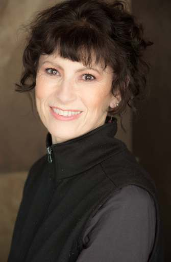 Dr. Paula Thomson, a white woman with dark hair, smiles at the camera, wearing a grey shirt, a black vest and some small earrings.