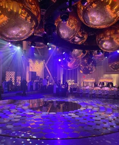 event production scene with round mirrored dance floor with round stickers, gold orbs handing from ceiling, and purple lights coming down from above