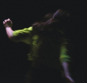 Blurry and dark, close-up image of dancer mid-movement taken from behind. She's wearing a neon yellow t-shirt and has a long ponytail. The details are out of focus.