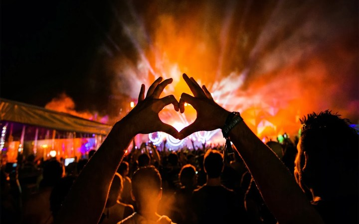 two hands coming together to form a heart at an EDM festival