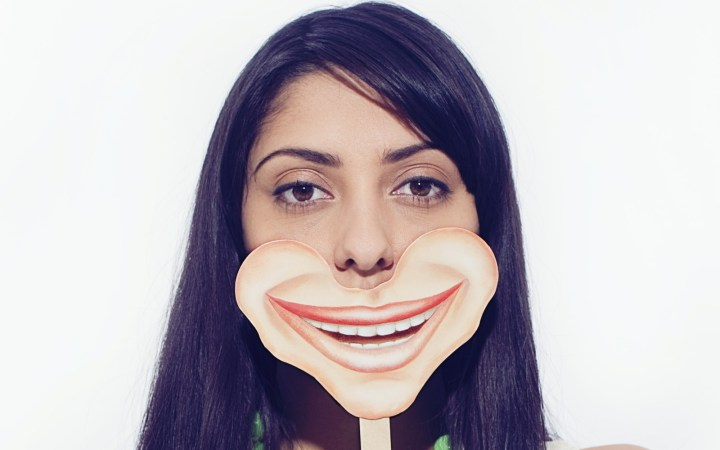 Woman in 20's Holding Smile Mask in Front of Face